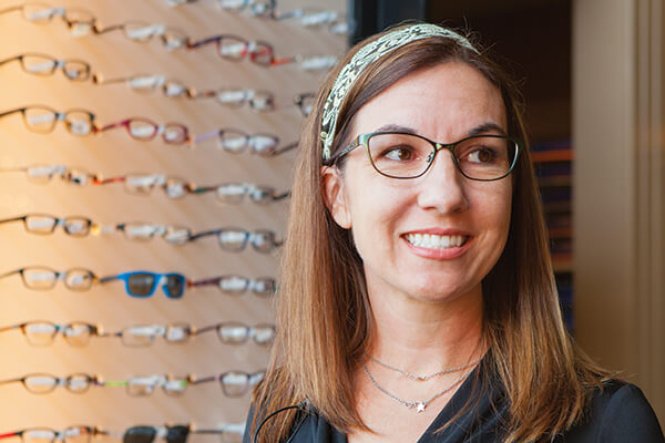 Woman trying on glasses in optical shop